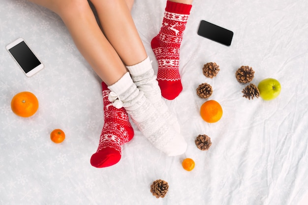 Soft photo of woman and man on the bed with phone and fruits, top view point. female and male legs of couple in warm woolen socks. christmas, love, lifestyle concept