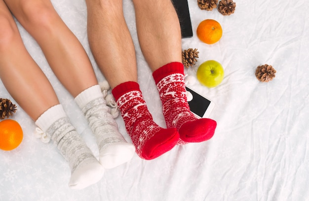 Soft photo of woman and man on the bed with phone and fruits, top view point. female and male legs of couple in warm woolen socks.