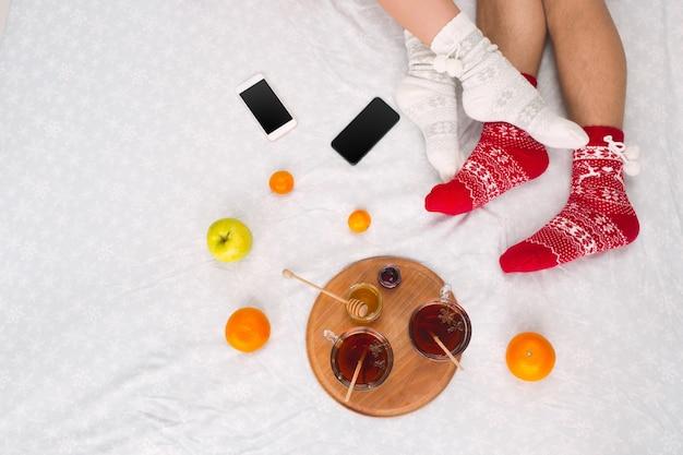 Foto morbida di donna e uomo sul letto con telefono e frutta, punto di vista dall'alto. piedini femminili e maschili di coppia in calzini di lana caldi.