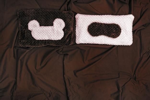 Soft pillow and sleep mask on dark crumpled sheet.
