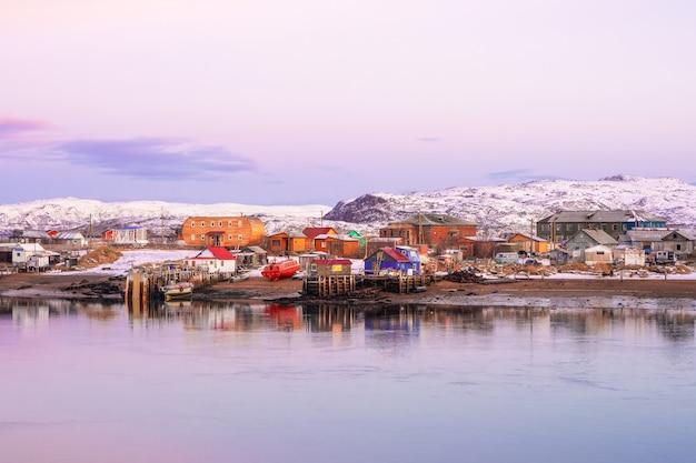 バレンツ海の海岸にある北極圏の村の柔らかなピンクのハーフトーン。冬のテリベルカの素晴らしい景色。ロシア。