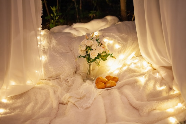 Мягкие пледы на траве, букет из роз, тарелка с круассанами, белый навес на елке.