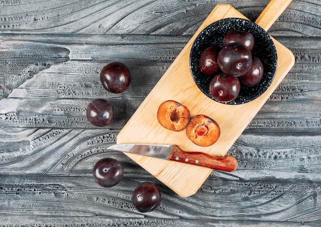 Soft plums with a fruit knife in a dish and wooden board on grey wood background, flat lay.