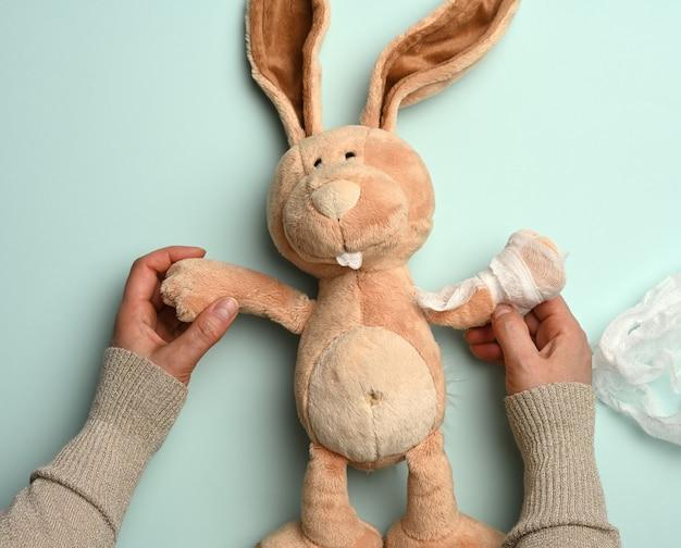 흰색 의료 붕대, 외상으로 붕대를 감은 발을 가진 부드러운 봉제 토끼