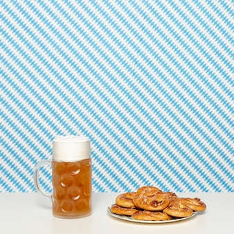 Soft pretzels and blonde beer on white table