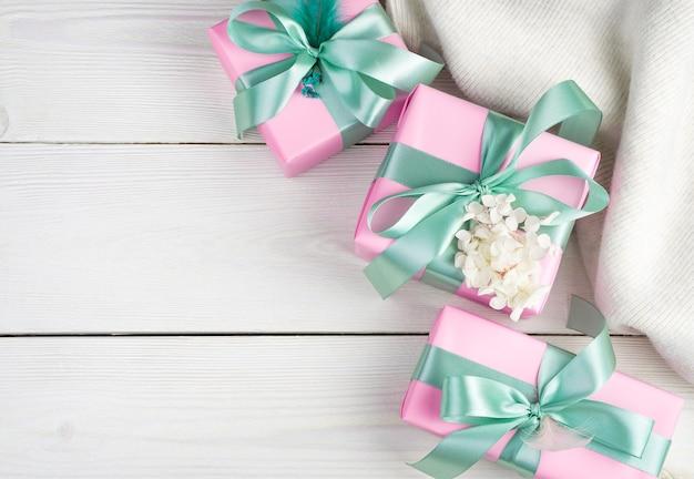 선물 상자와 밝은 나무 배경에 흰색 스웨터와 부드러운 낭만적 인 배경. 평면도