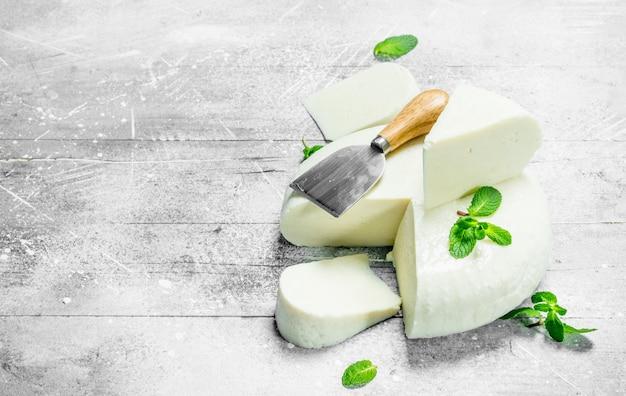 新鮮なミントの葉と柔らかい羊のチーズ。素朴な背景に。
