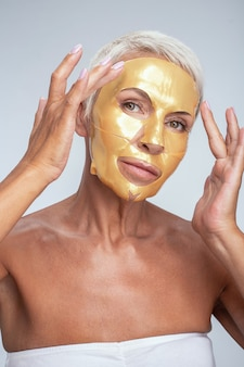 Soft skin. cute blonde putting golden mask on her face while taking care of her skin