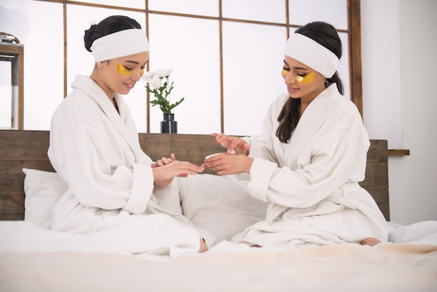 Soft skin. joyful attractive pleasant women sitting together and applying cream on their hands
