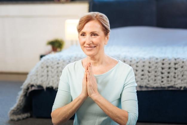優しい笑顔。接続された手で座っている間、自宅で朝の瞑想をしている美しい明るい髪の女性