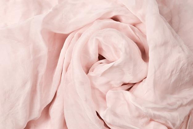 Мягкий гладкий розовый фон шелковой ткани. текстура ткани.