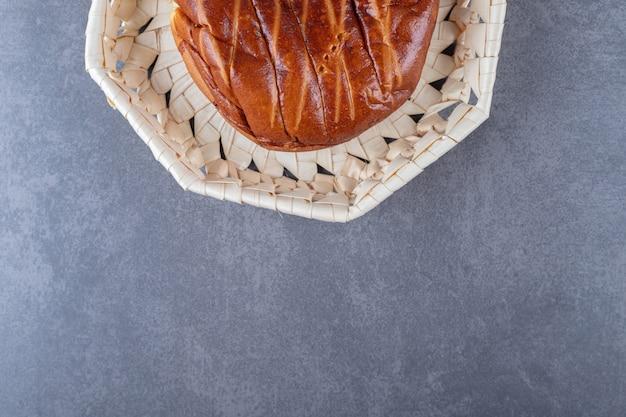 大理石のテーブルの籐のバスケットの柔らかい甘いパン。