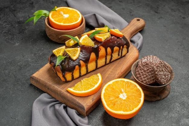 柔らかくておいしいケーキは、木製のまな板にビスケットと暗い背景にタオルでレモンをカットします
