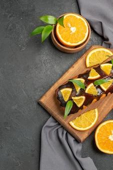 柔らかくておいしいケーキは、木製のまな板にビスケットと暗いテーブルにタオルでレモンをカットします