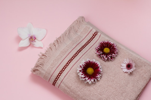 Soft terry towel with white orchid and red flower buds on pink background. top view.