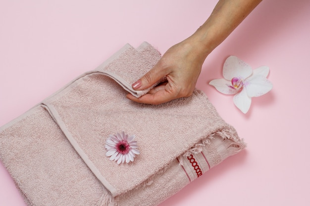 Soft terry towel and woman's hand with flowers on pink background. top view.