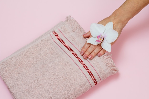 Soft terry towel, woman's hand with white orchid flower on pink background. top view.