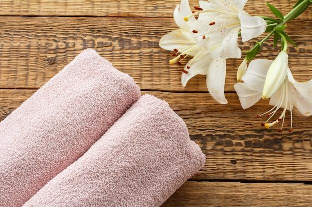 古い木の板に白いユリの花の花束と柔らかいテリータオル。上面図。
