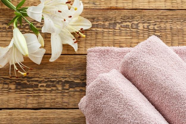 木の板に白いユリの花の花束と柔らかいテリータオル。上面図。