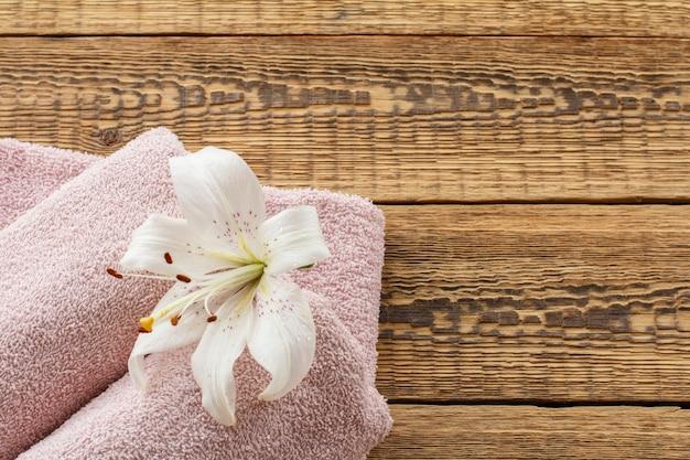 古い木の板に白いユリの花が付いた柔らかいテリータオル。上面図。