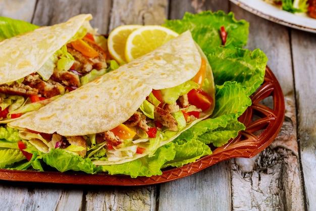 Мягкие лепешки, фаршированные салатом, мясом и сыром на деревянной поверхности