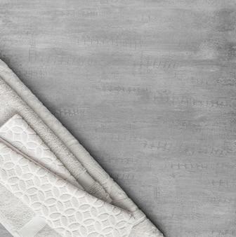 灰色の装飾的なスタッコの背景の柔らかいタオル。上面図、分離