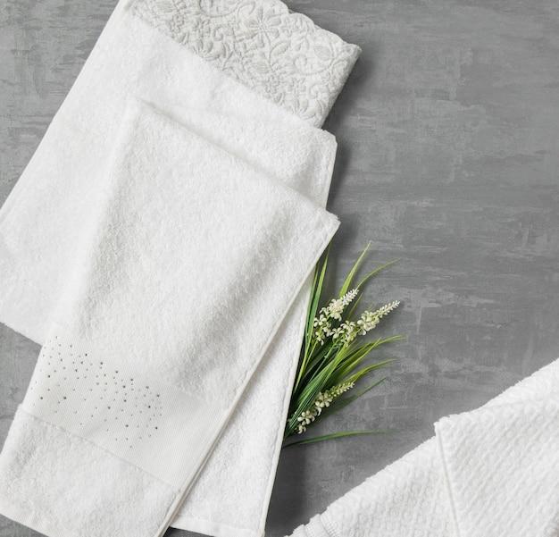 灰色の装飾的なスタッコの背景に花が付いている柔らかいタオル。上面図、分離