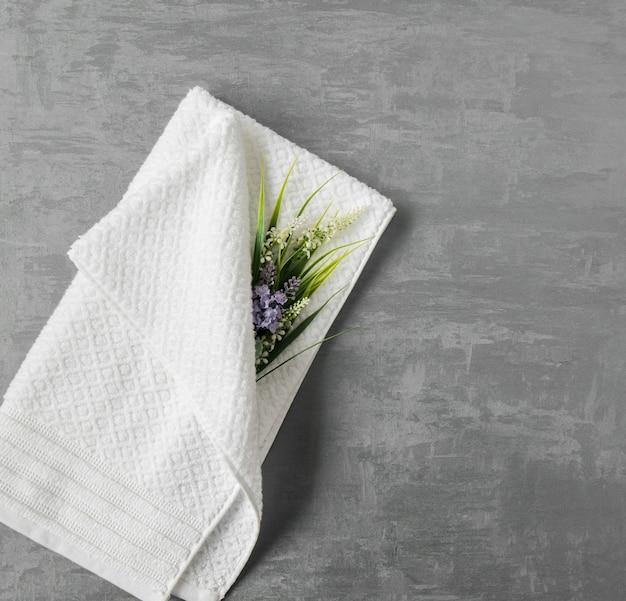 회색 장식 치장 벽토 배경에 꽃이 있는 부드러운 수건. 상위 뷰, 절연