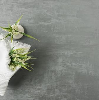 Мягкое полотенце с цветком на сером фоне декоративной лепнины. вид сверху, изолированные