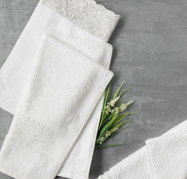 Soft towel with a flower in a grey  decorative stucco background. top view, isolated