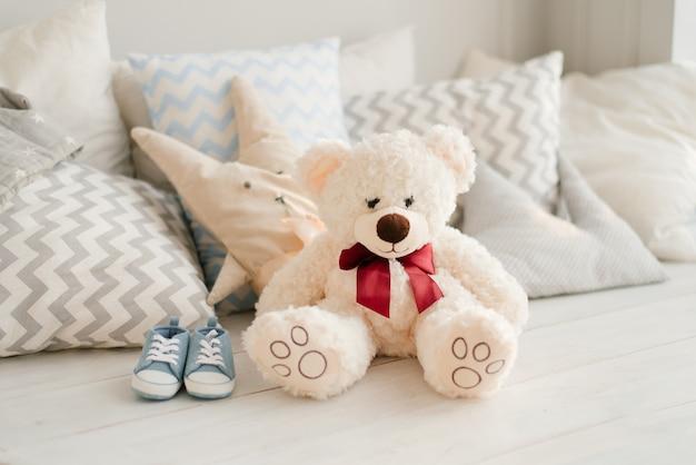 Мягкая игрушка медведь и синие кроссовки будущего малыша на кровати в подушках