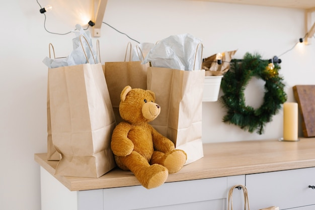 Soft toy bear near craft paper bags and christmas wreath