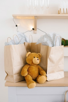 Soft toy bear near craft paper bags