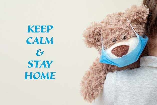 Soft toy bear with protective medical mask on child shoulder with words keep calm, stay home. health care and virus protection concept.