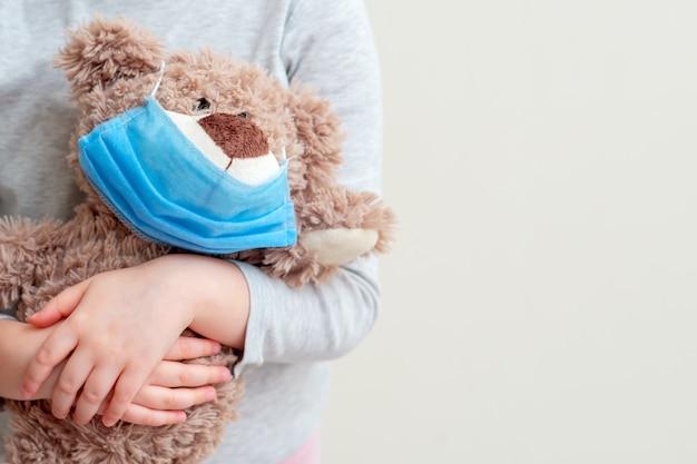 白い背景の上の子供の手に保護医療マスクとぬいぐるみクマ。ヘルスケアとウイルス対策の概念。