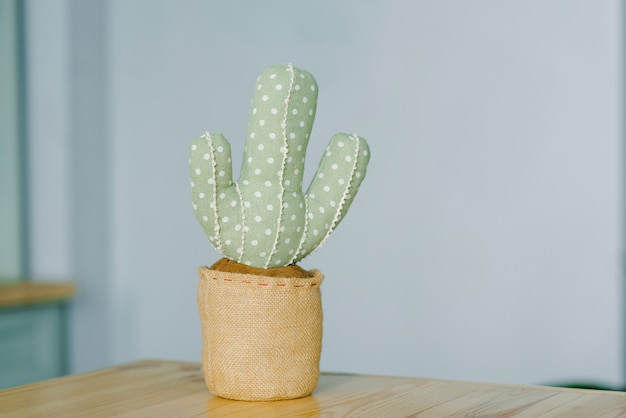 Soft toy cactus on a wooden shelf
