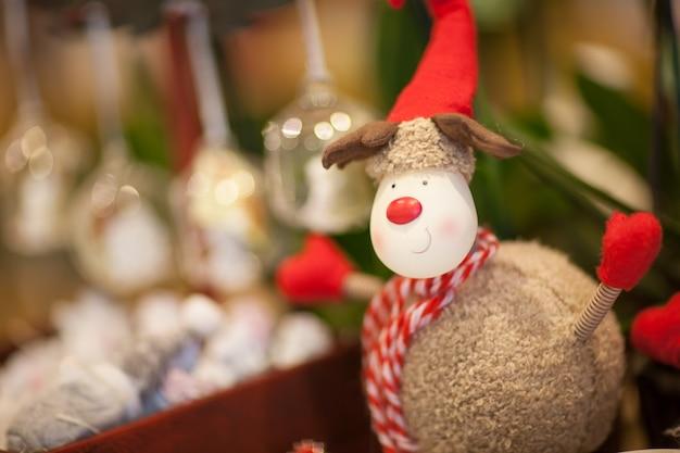 ぼやけた背景に赤いスカーフと帽子のぬいぐるみクリスマストナカイ