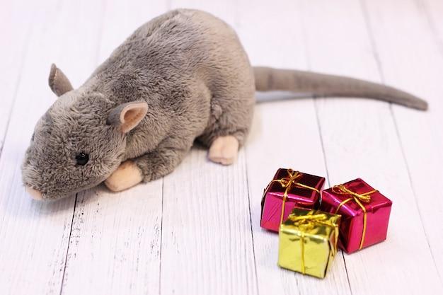 Мягкая игрушка серая крыса возле новогодних украшений в виде подарков