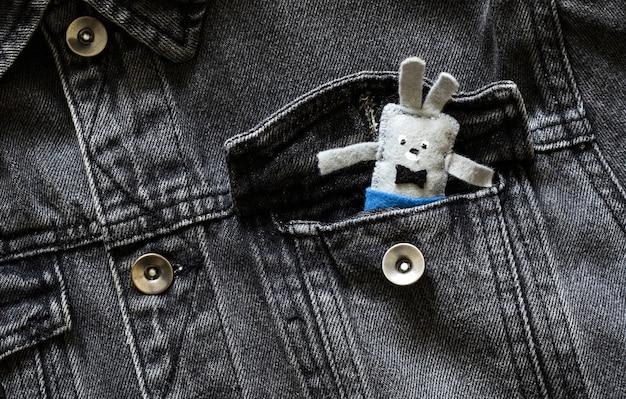 Мягкая игрушка заяц торчит из кармана джинсовой куртки