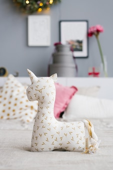 Soft toy or pillow in the form of a unicorn on the bed, decorated for christmas