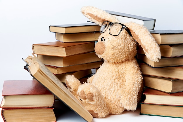 A soft toy rabbit in glasses sits in piles of books and reads a book.