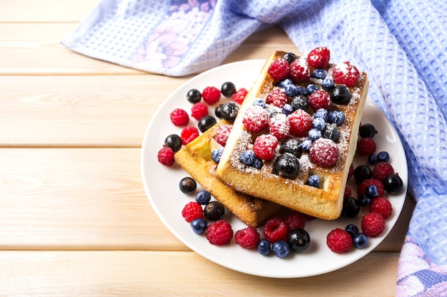 Soft waffle with blueberry and raspberry on blue linen napkin