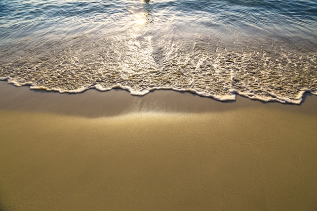 Soft wave of blue ocean on sandy beach background with sunset natural tone. holidays and summer concept.