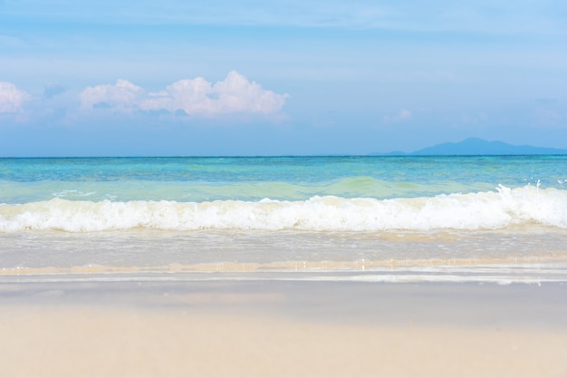 Soft wave of ocean on sand beach with blue ocean sea and sky in summer vacation.