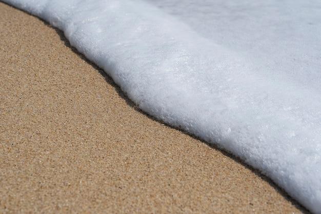 晴れた日の白いきれいな泡と砂浜の海の柔らかい波。自然の概念