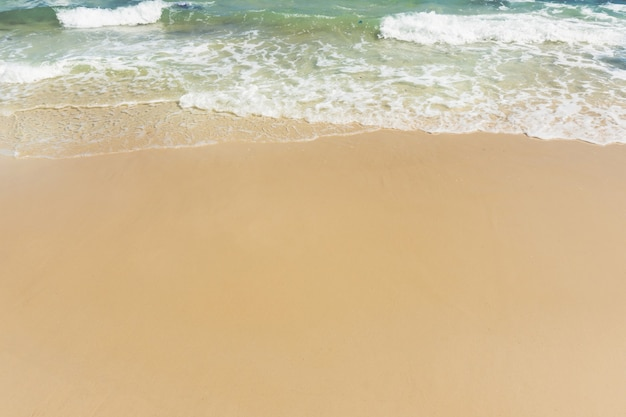 Soft wave of sea on empty sandy beach background with copy space