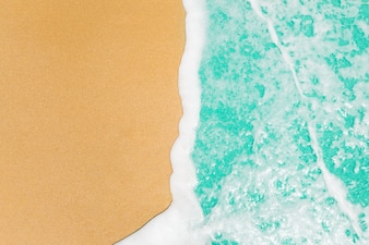 Soft waves with blue ocean sea on golden sand with copy space.