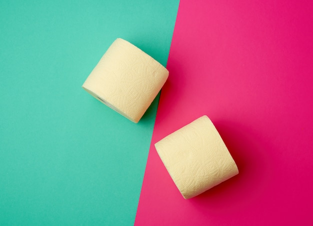 Soft yellow toilet paper in a roll on a green-pink background