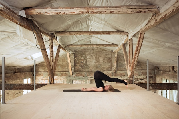 Soft. a young athletic woman exercises yoga on an abandoned construction building. mental and physical health balance. concept of healthy lifestyle, sport, activity, weight loss, concentration.