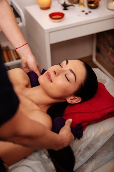 Softly stroking. pleasant good-looking woman relaxing with closed eyes while workers healing body with herbal bags